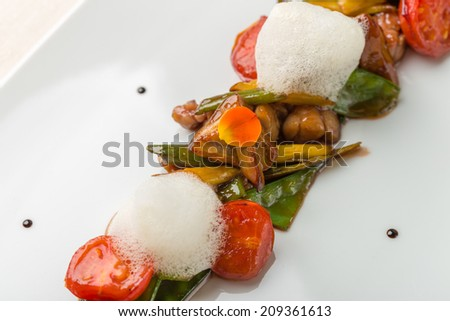 Warm salad with sweetbread, peaches, tomatoes and mousse. Fine cuisine. Close up