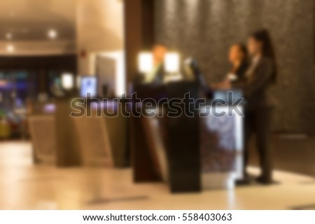 Warm toned image of Defocused blur of hotel lobby front desk with unrecognizable people.