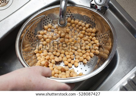 Washing chickpeas under running water in a colander