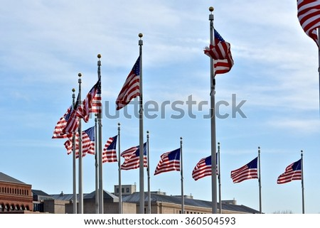 WASHINGTON DC, USA - DECEMBER 27, 2015: USA flags surround the Washington monument at the National Mall. The National Mall is a national park in downtown Washington, D.C.