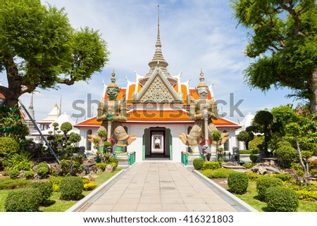 Wat Arun Raj Tharam - Two giant statues holding their batons in front of the temple entrance, Bangkok, Thailand.