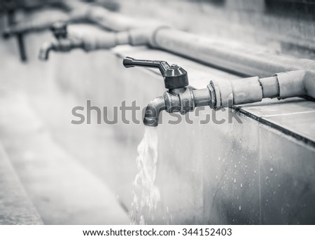 Water drop from chrome faucet and water pipeline background. Wash Basin ceramic tile at bathroom. Drink water plumbing pipeline. Resource conserve concept.