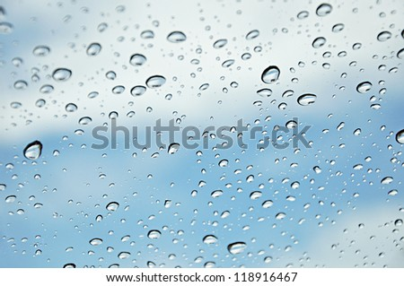 Water drops on the glass in blue sky background