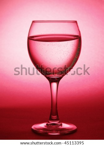 Water in glass on pink