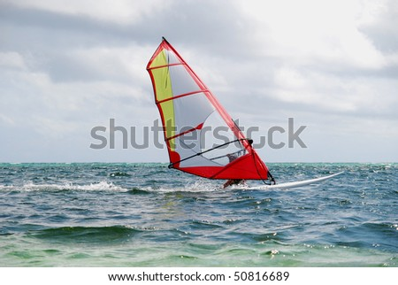 water sports: windsurfer with bright colored sail in Philippines blue water