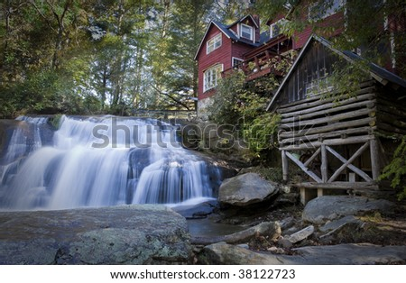 Waterfall in forest with house and log cabin