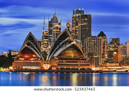 Waterfront cityline of Sydney city downtown at sunrise with bright illumination of modern architectural landmarks