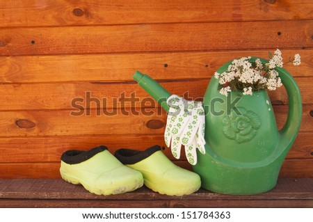 watering can and rubber boots on background texture of wood