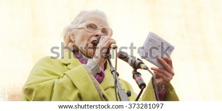 Elderly woman in headphones. Lady smiling and singing. Music and mood. Tune of my life.