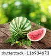 Watermelon with a slice and leaves on a wooden table. Background - blur of nature. - stock photo
