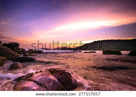 Waves crashing on rocky shore in sunset
