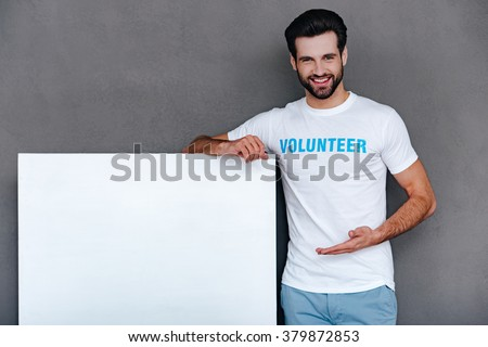 We can help to community! Confident young man in volunteer t-shirt pointing on white boardand looking at camera with smile while standing against grey background