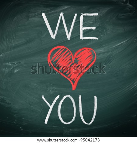 We Love You. Handwriiten message in chalk on a blackboard incorporating a red heart symbol for love.