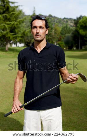 Wealthy man in sport clothes holding golf driver while observe the direction of ball, handsome wealthy man in polo t-shirt standing on golf course, success attractive man playing golf on holidays