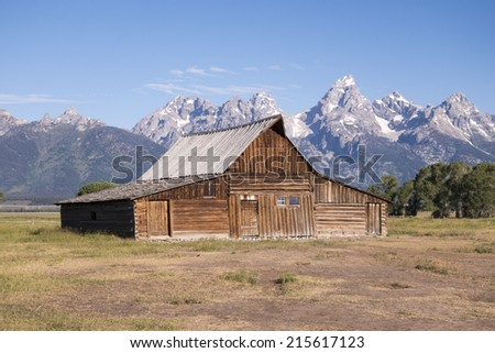 weathered barn with mountain backdrop