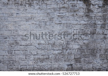 Weathered stained old brick wall background. Texture of an ancient wall of several floors with lots of rows of bricks