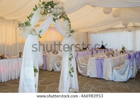 Wedding arch decorated with veil and flowers.