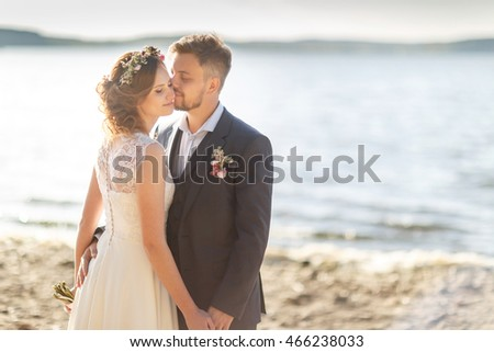 Wedding; Beautiful Romantic Bride and Groom Kissing  near the beach