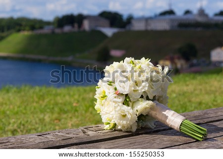 wedding bouquet with white roses laying on bench