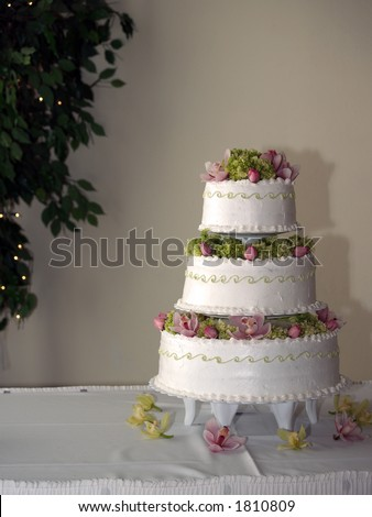 Wedding Cake with Flowers and Greens with Lighted Tree in Background