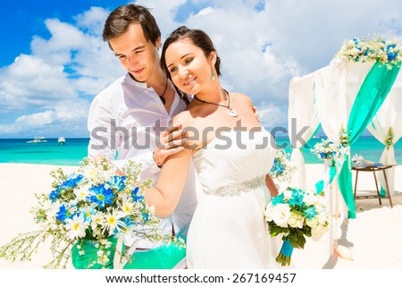 Wedding ceremony on a tropical beach in blue. Happy groom and bride under the arch decorated with flowers on the sandy beach. Wedding and honeymoon concept.