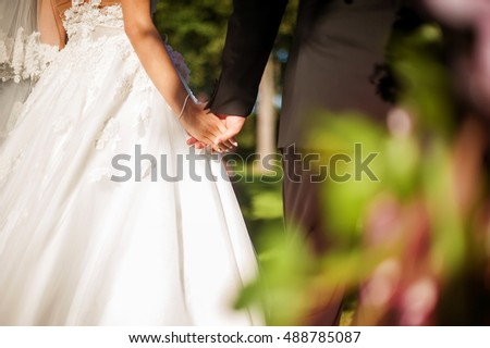 Wedding couple bride and bridegroom holding hands