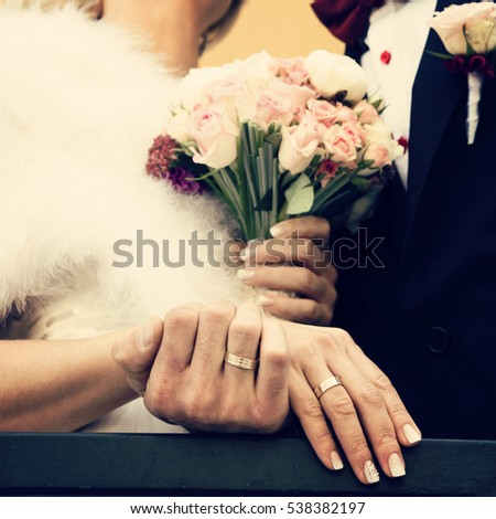 Wedding details, close up of hands with wedding rings and wedding bouquet