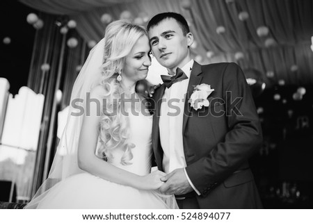 Wedding. Groom kisses the bride in luxury apatment. Wedding day. Bridal bouquet