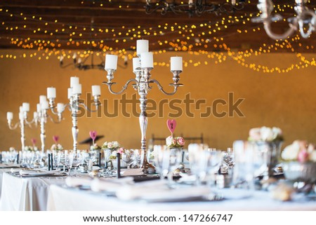 Wedding reception hall with decor including candles, cutlery and crockery; selective focus on candelabra