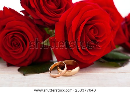 Wedding rings and wedding bouquet of red roses on wooden table, horizontally Selective focus, the background is blurred