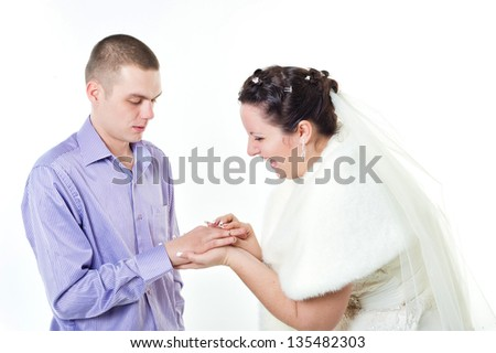 Wedding rings. Bride putting a wedding ring on groom's finger.