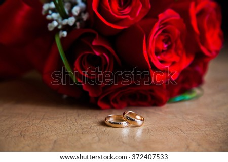 Wedding rings on the table wedding rings on a background of a bouquet of red roses