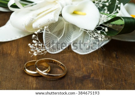 Wedding rings with calla bouquet on wooden background