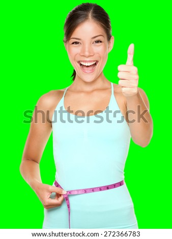 weight loss woman smiling happy excited standing with measuring tape giving thumbs up success hand sign isolated cutout on green chroma key background. Asian female fitness model.