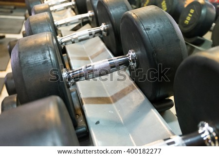 Weights Dumbbells on steel stand in fitness gym