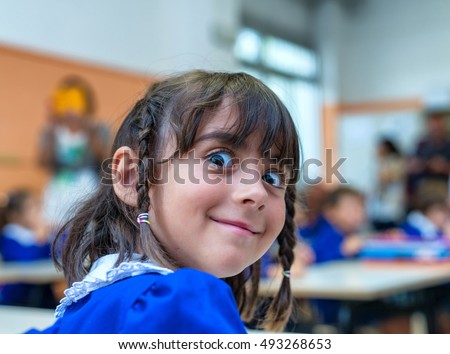 Weird face of elementary schoolgirl in classroom.