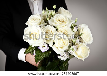 well-dressed man holding a bouquet of flowers. Holidays and celebrations. Wedding day.