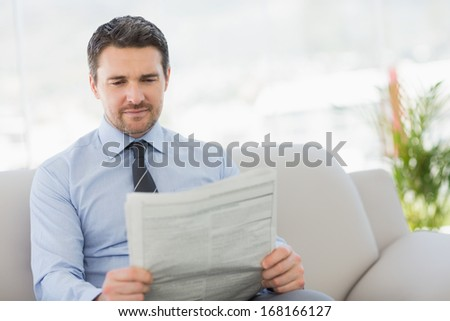 Well dressed relaxed young man reading newspaper on sofa in the house