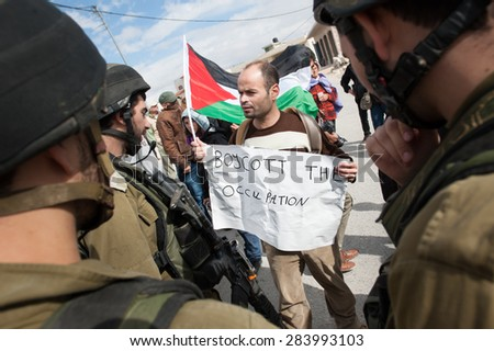 "WEST BANK, OCCUPIED PALESTINIAN TERRITORIES - NOVEMBER 9: A Palestinian with a sign, ""Boycott the Occupation"", faces Israeli soldiers in a protest in Al Ma'sara, West Bank, November 9, 2012."