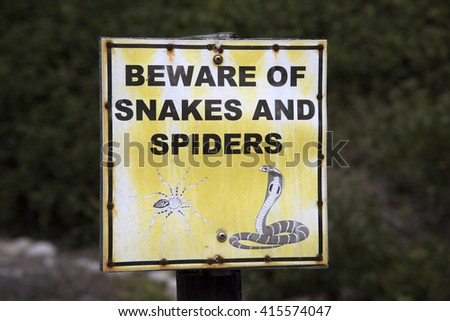 WESTERN CAPE SOUTH AFRICA - APRIL 2016 - A roadside warning sign 'Beware of Snakes and Spiders' placed where extra care should be taken in this high risk Southern African area