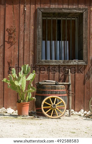 Western style wall, window of hut with barrel, wheel, cactus