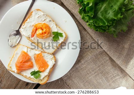 Wheat bread toasts with cream cheese, smoked salmon and shrimp selective focus horizontal top view