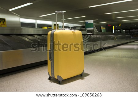 Wheeled suitcase in airport terminal baggage claim area