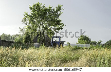 Wheeled tractor stands near wooden house with tall weed growth before. Bulatovo village, Kaluzskaya region, Russia.