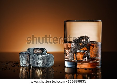 Whiskey glass and ice cubes on black surface with warm background