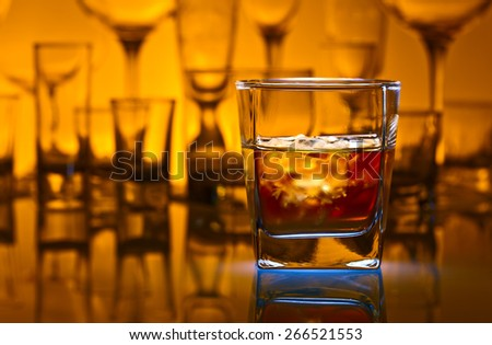 whiskey with natural ice on glass table in bar