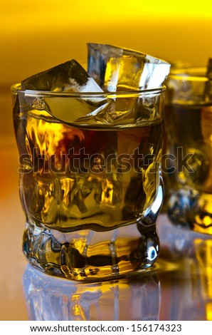 whisky with ice on a white reflexive background.