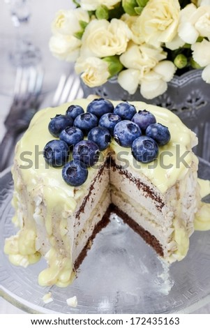 White and dark chocolate layer cake decorated with blueberries