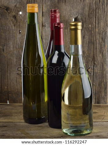 White And Red Wine Bottles On Wooden Background