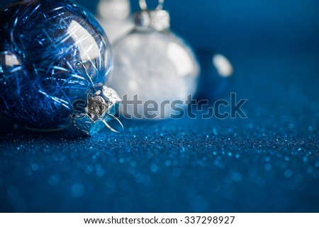 White and silver christmas ornaments on dark blue glitter background with space for text. Merry xmas card. Winter holiday theme. Happy New Year.